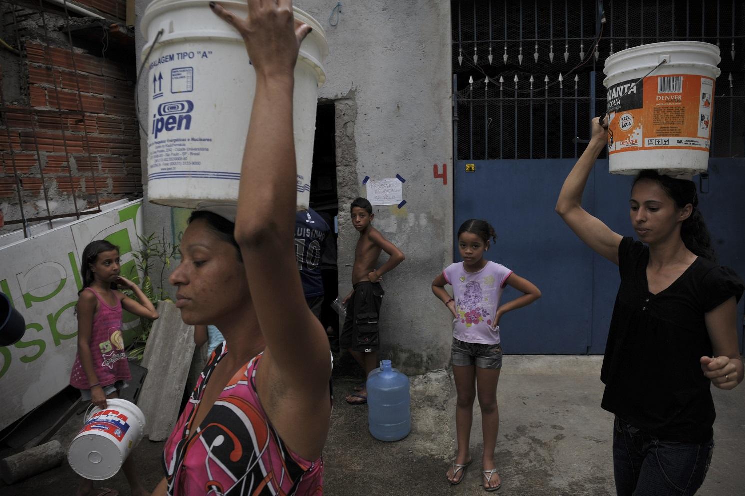 Mulheres carregam baldes na cabeça na favela de Paraisópolis, em São Paulo: acesso a água precisa ser universalizado. Foto Maurício Lima/AFP