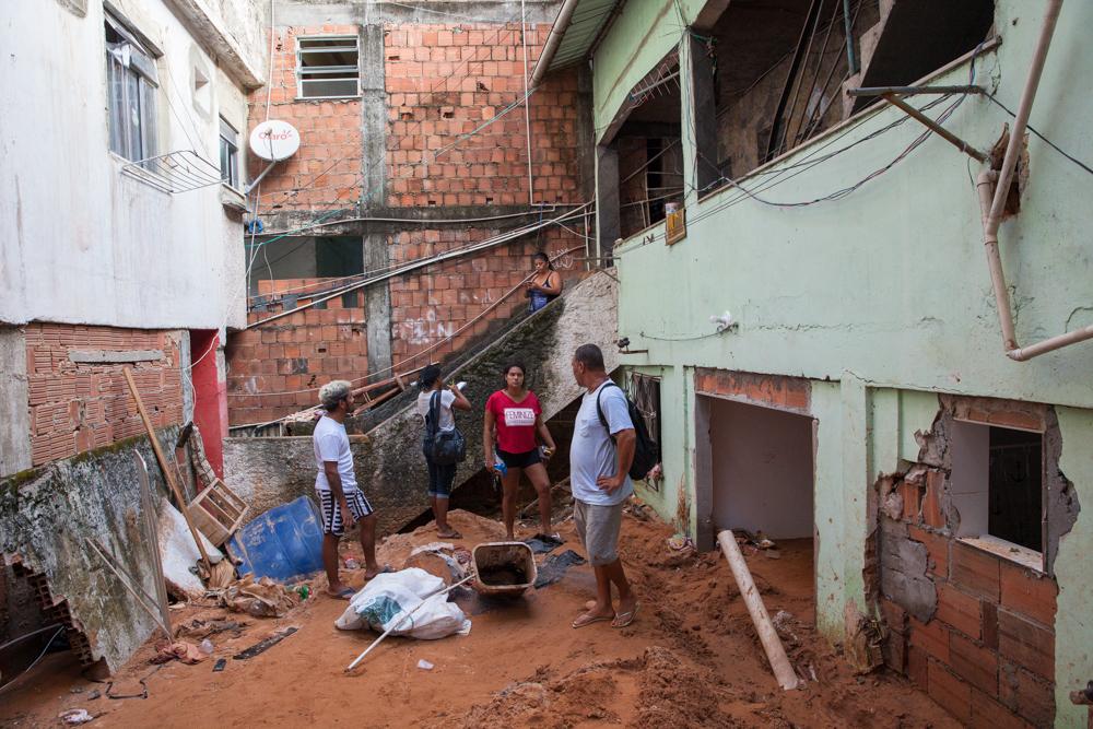 Sobre o monte de terra que soterrou a casa de Clarencio (de costas), voluntários cadastram moradores atingidos pela chuva (Foto Kita Pedroza)