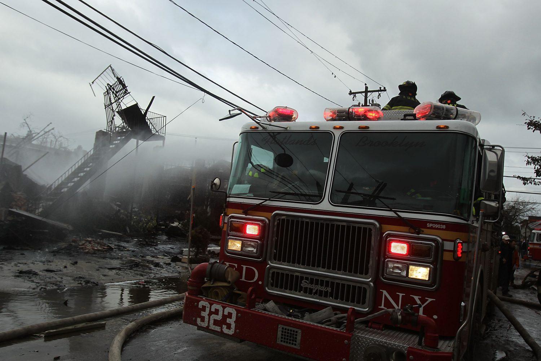 Bombeiros trabalham no rescaldo de um incêndio provocado pelo furacão Sandy em Nova York. Foto Spencer Platt/Getty Images/AFP