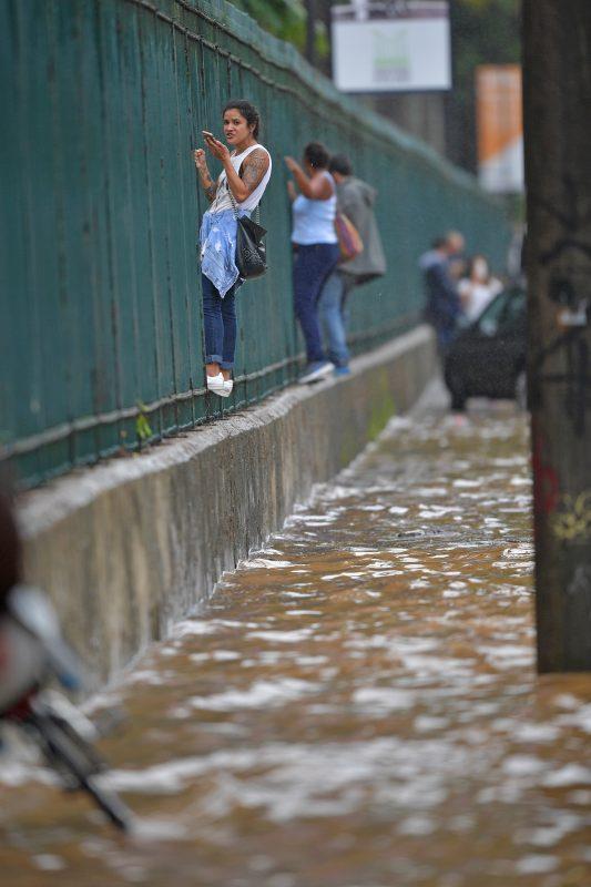 Mulheres se penduram nas grandes do Jardim Botânico para fugir das ruas alagadas. Foto Carl de Souza/AFP