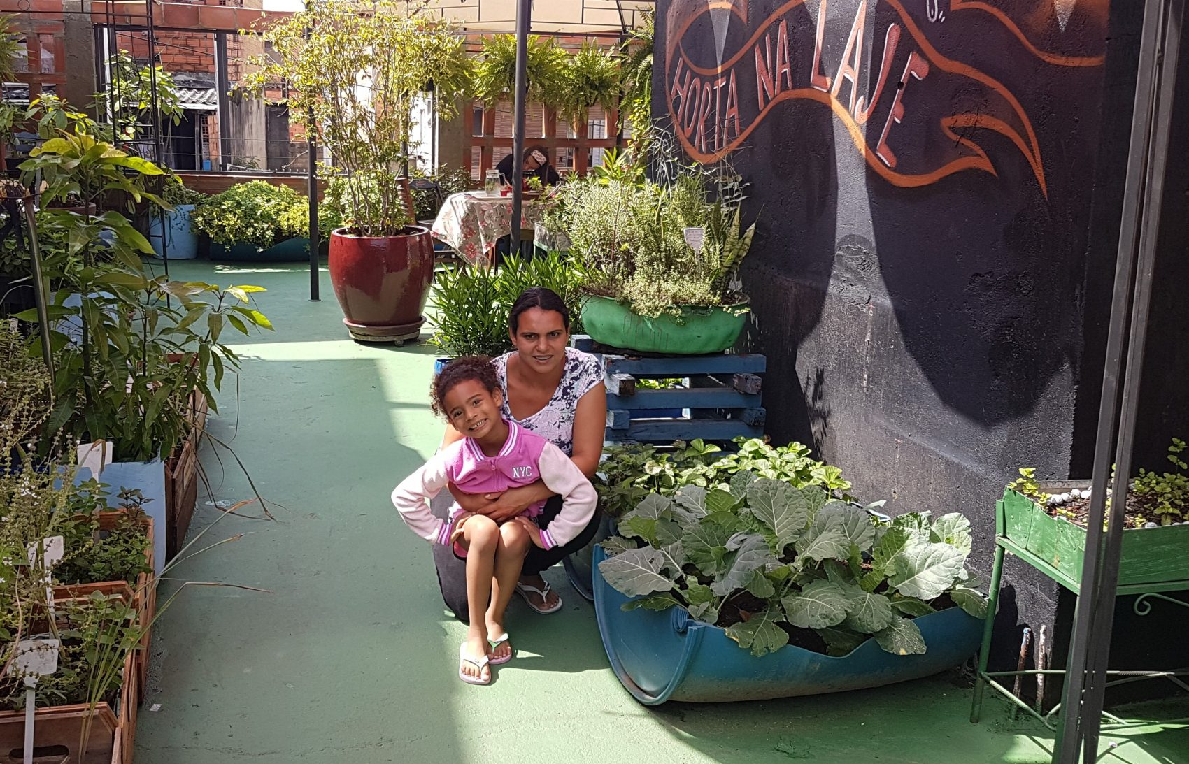 Natália com a filha Júlia: horta com manjericão, alface, rúcula e coentro na sua laje em Paraisópolis após passar pelo projeto (Foto: Florência Costa)