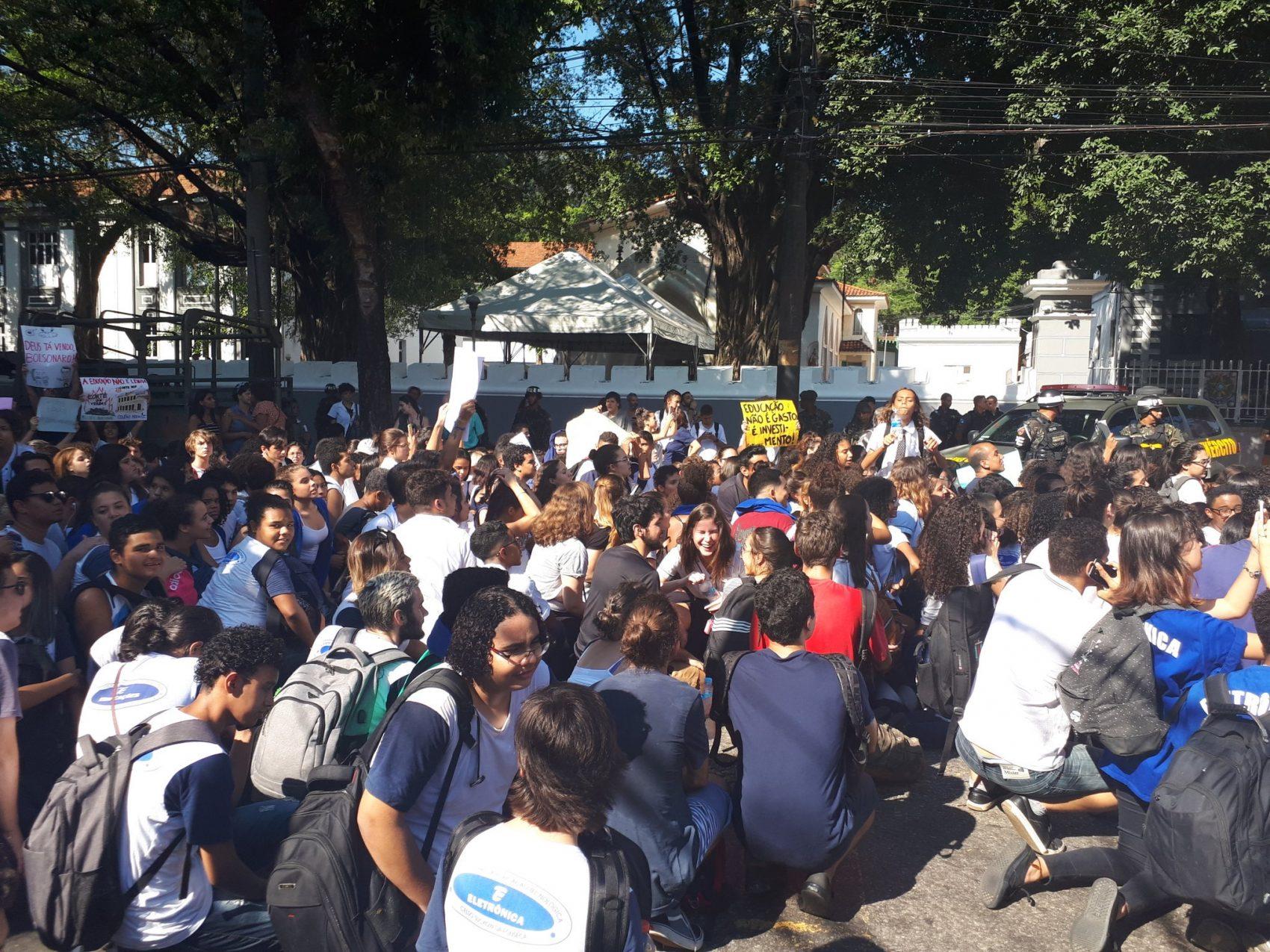 Estudantes sentam no meio da rua em frente ao Colégio Militar para protestar contra o presidente Jair Bolsonaro por corte de verba (Foto: Twitter)