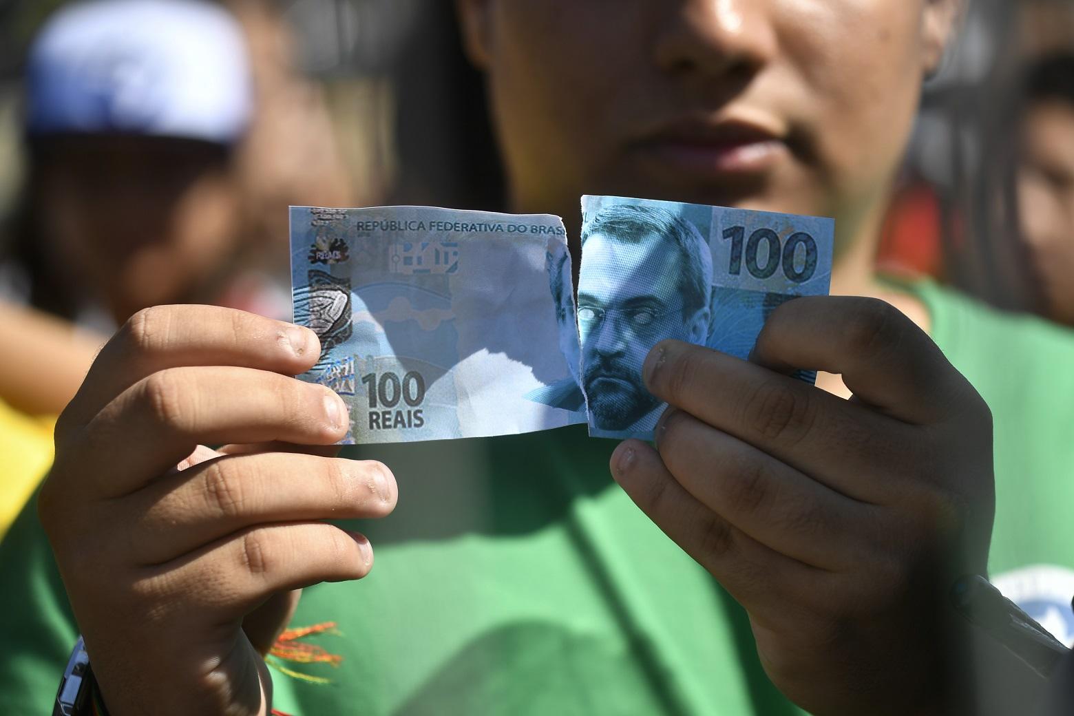 Manifestante rasga cédula falsa com a foto do ministro Abraham Weintraub. em protesto em frente ao MEC: críticas a criação de fundo de natureza privada para financiar educação pública (Foto: Mateus Bonomi/AGIF)