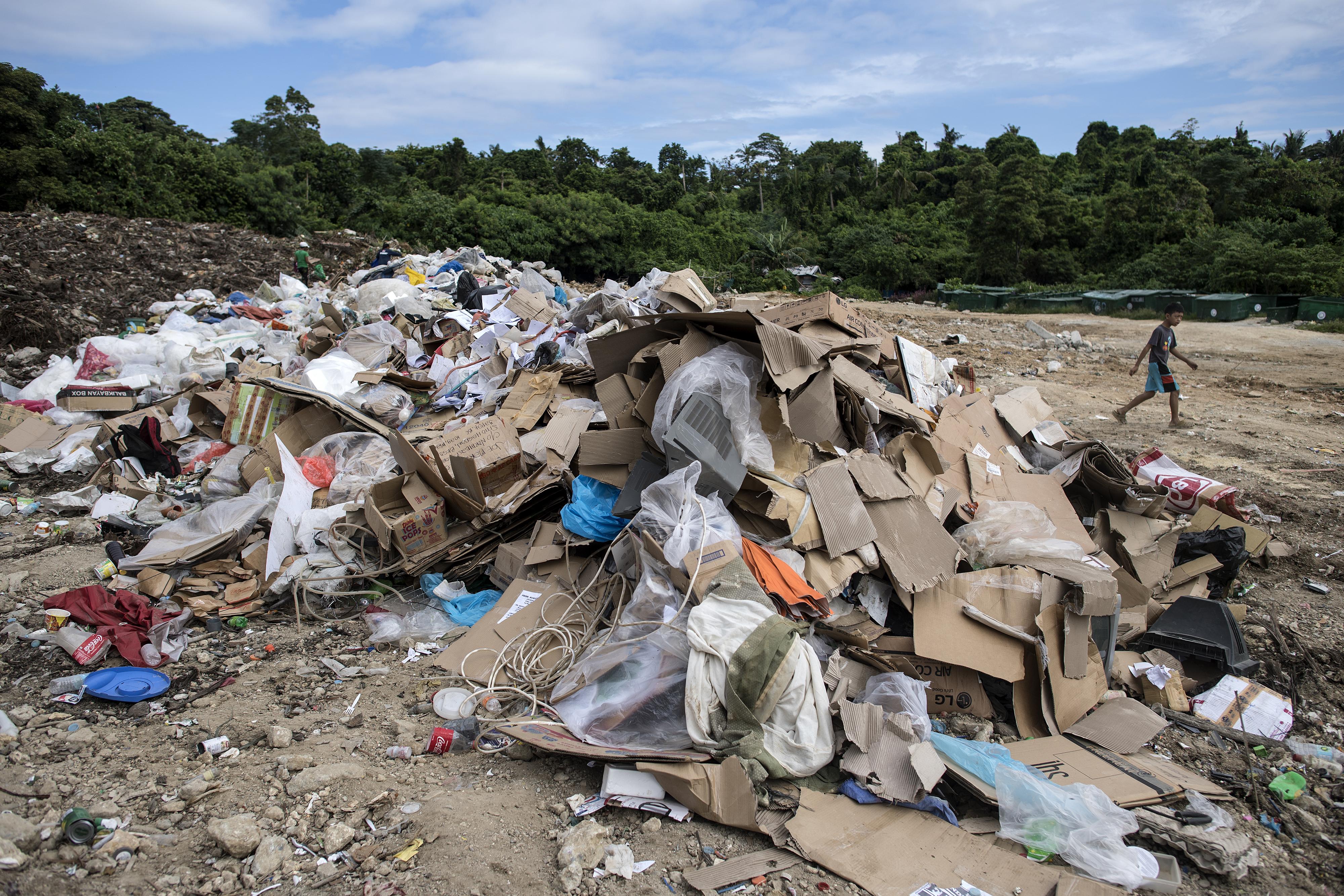 Criança passa ao lado de gigantesca pilha de lixo ilha Boracay, nas Filipinas: fechamento compulsório ao público. (Foto de Noel Celis (AFP)