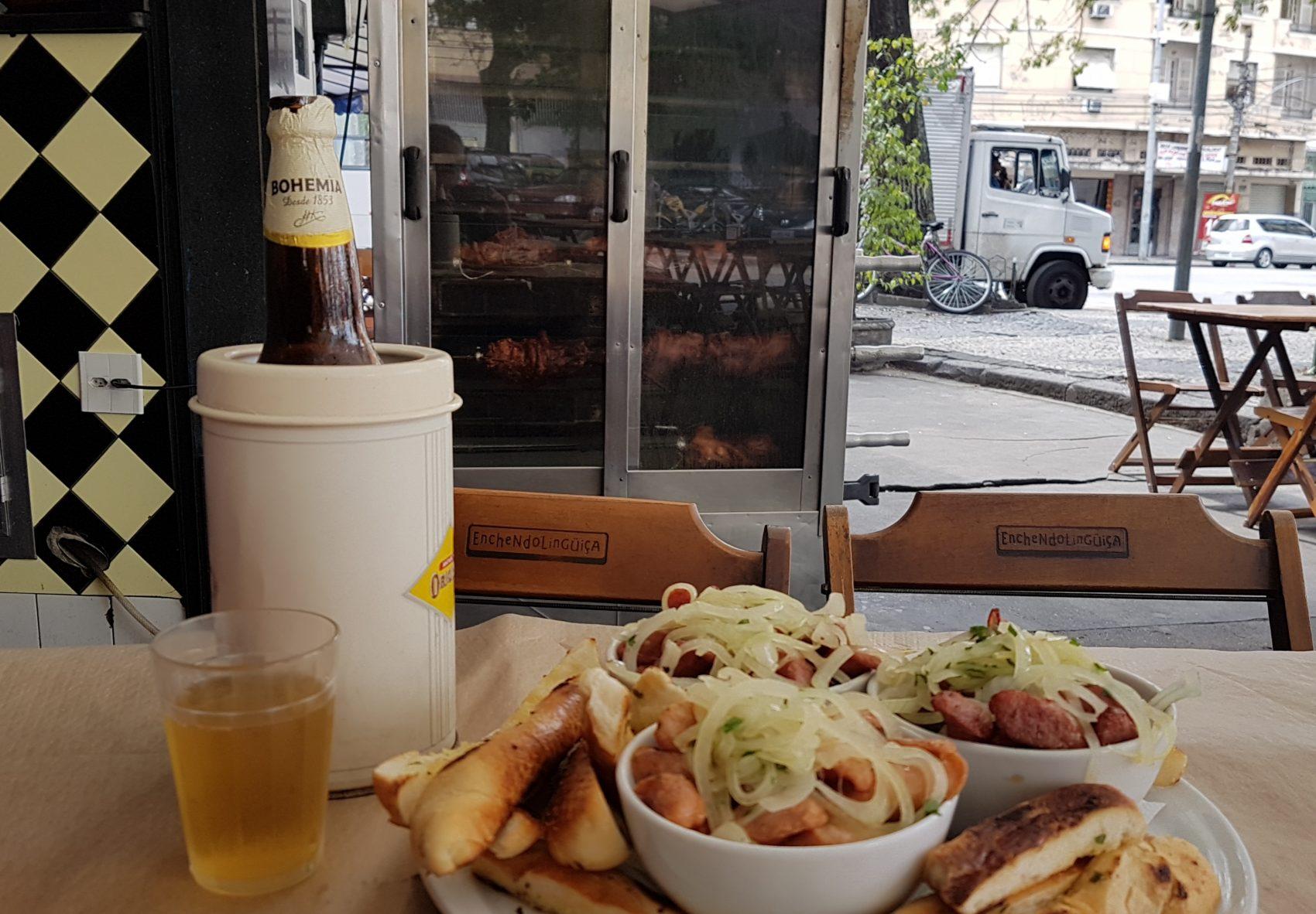 Três tipos de linguiça, cerveja e a vista joelho de porco girando na assadeira: atrações do bar Enchendo Linguiça, no Grajaú (Foto: Oscar Valporto)