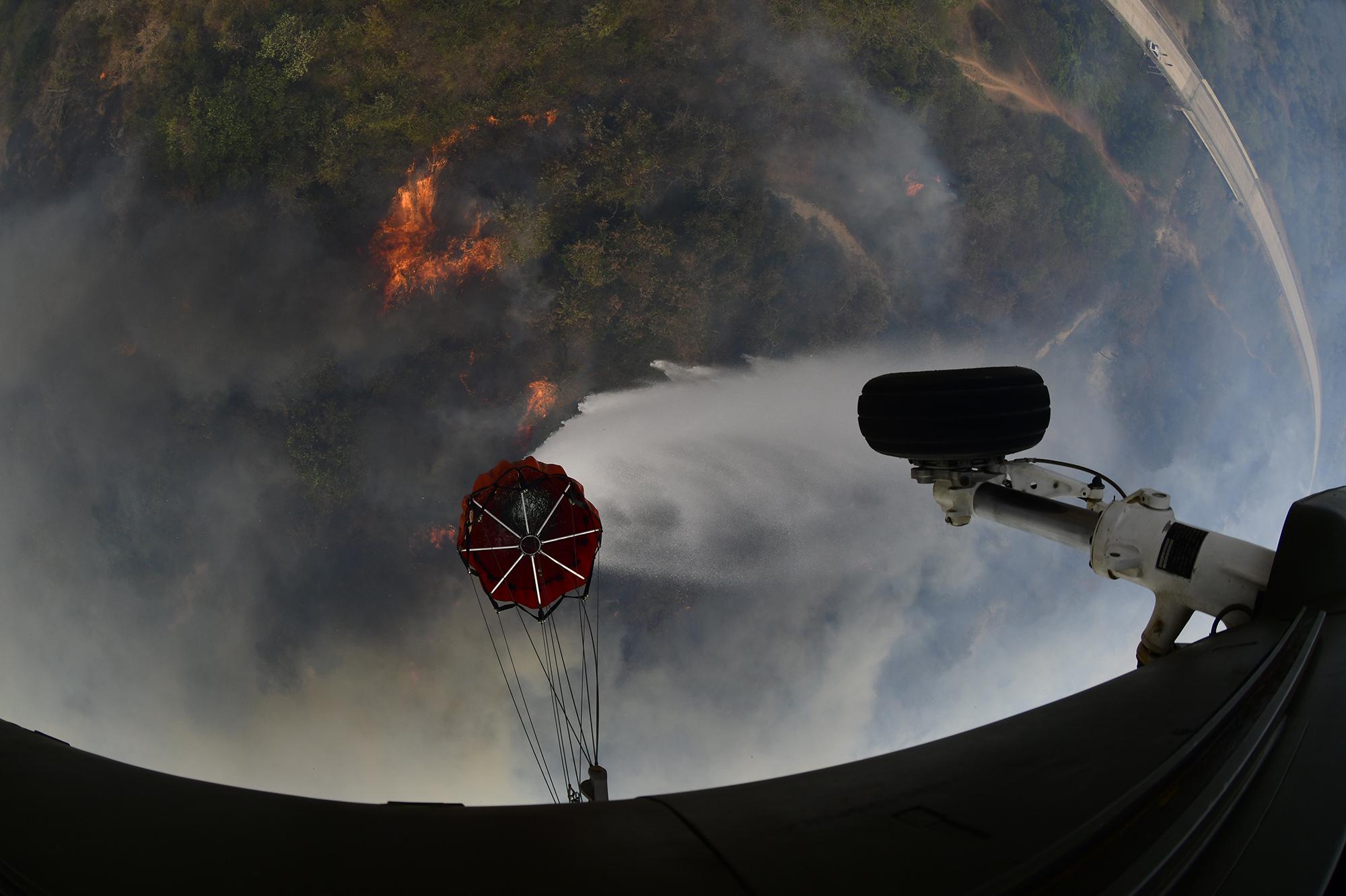 Helicóptero militar despeja água de bolsa para tentar apagar queimadas na região de Roboré. na Bolívia. Foto de Carlos Orias B