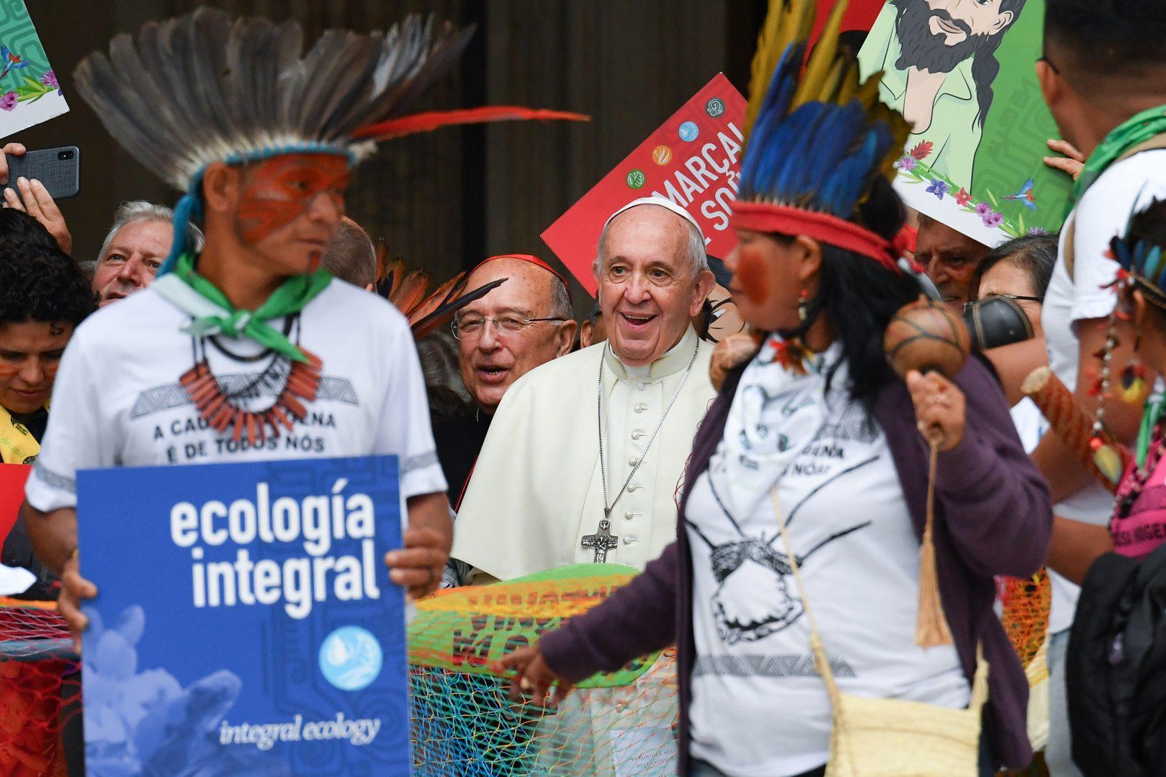 """O Papa Francisco com representantes de povos indígenas da Amazônia após a missa de abertura do Sínodo no domingo: """"qual é a diferença entre ter plumas na cabeça e o chapéu de três pontas utilizado por certas hierarquias em nossos dicastérios?"""" (Foto: Andreas Solaro/AFP)"""