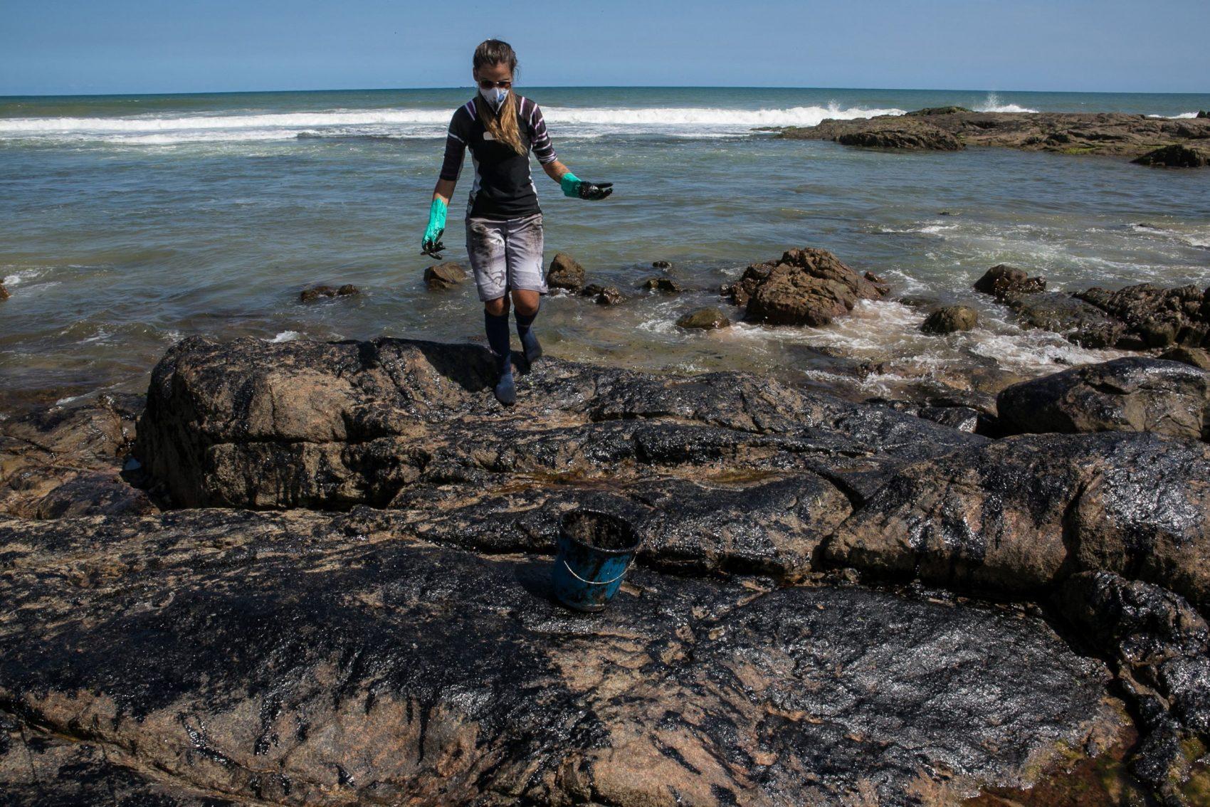 Ambientalista tira óleo das pedras da Pedra do Sal, em Salvador: Marinha teme que mais toneladas de óleo cheguem às praias brasileiras (Foto: Antonello Veneri/AFP)