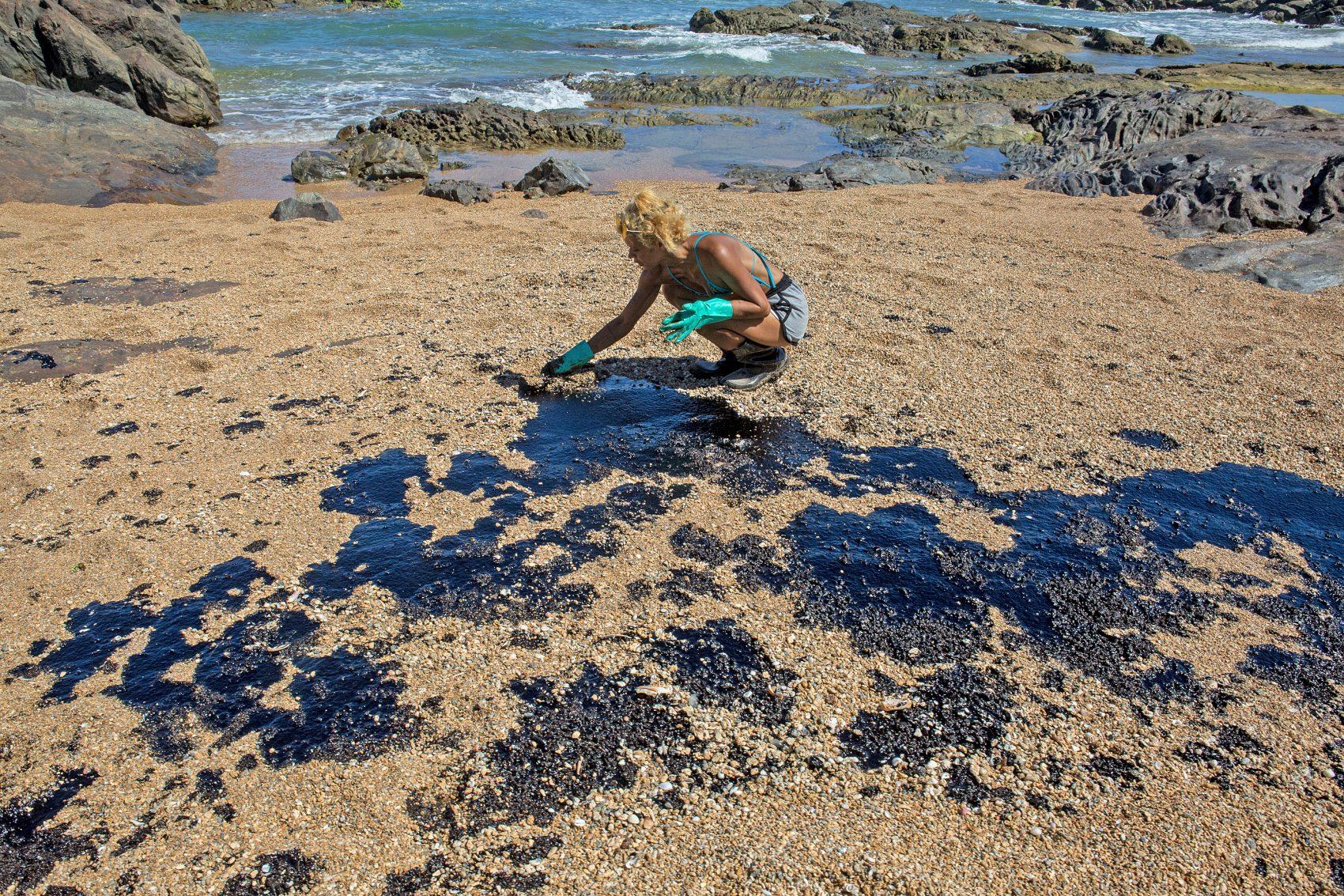 Voluntária retira óleo da praia de Busca Vida, perto de Salvador: Bahia foi o estado com mais localidades atingidas pelo desastre ambiental (Foto: ANTONELLO VENERI / AFP)