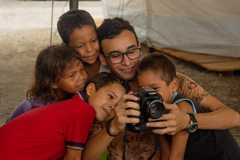 Integrante do projeto Estórias Migrantes com crianças venezuelanas em abrigo de Boa Vista: equipe compartilha experiências com a comunidade de migrantes (Foto: Kataryna Górka)