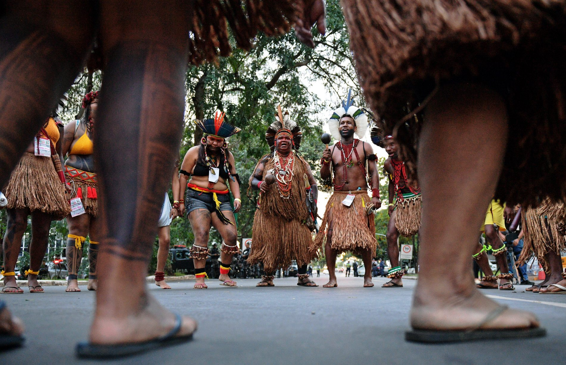 Brazilian indigenous men perform a ritual dance during a protest against the government's decision not to recognize the land demarcation of indigenous people living in Raposa Serra do Sol, Roraima State, in Brasilia, on April 25, 2018. - About 2,500 indigenous people from different tribes are taking part in the Indigenous National Mobilization (MNI) week - a mobilization which seeks to tackle territorial rights' negotiations with the government. (Photo by CARL DE SOUZA / AFP)