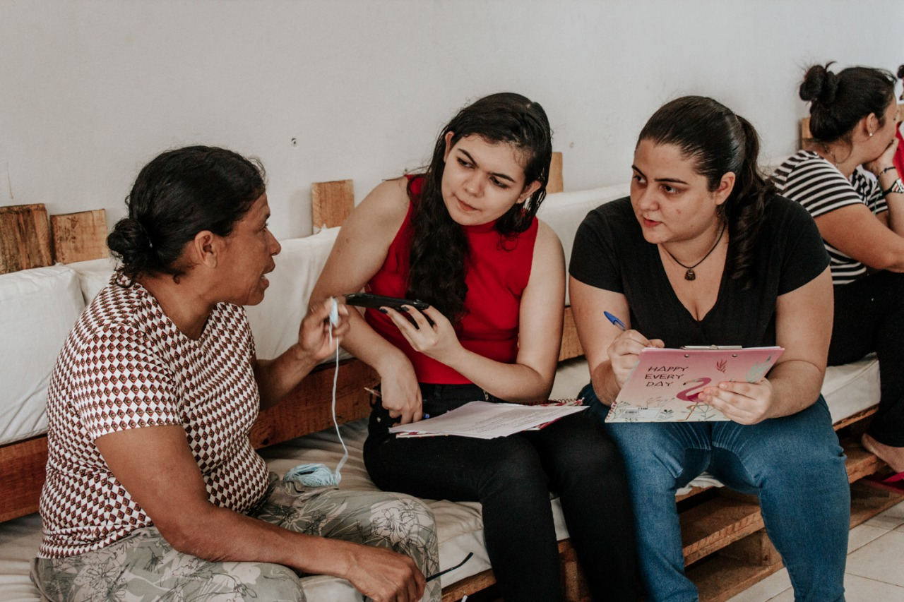 As estudantes Ana Clara Bernardes e Amanda Barros, integrantes do projeto, entrevistam venezuelana: projeto já fez entrevistas com mais de 50 migrantes e refugiados (Foto: Suedy Lorenna)