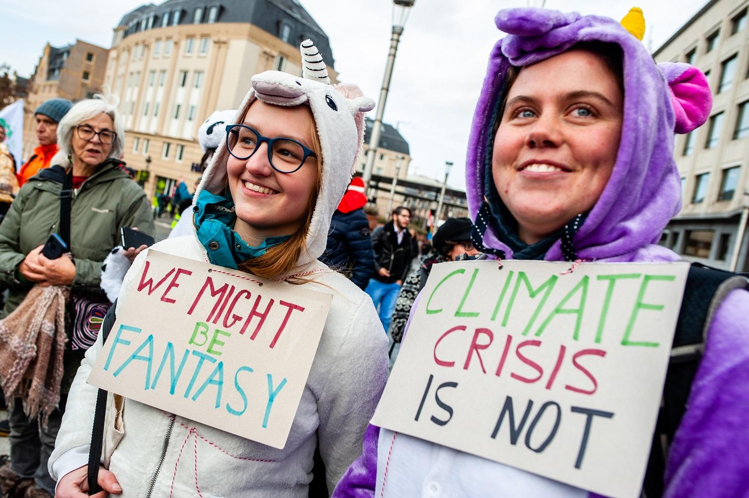 Em Bruxelas, duas manifestantes tentam explicar que a crise climática não é uma fantasia. Foto Arroyo Fernandez/NurPhoto