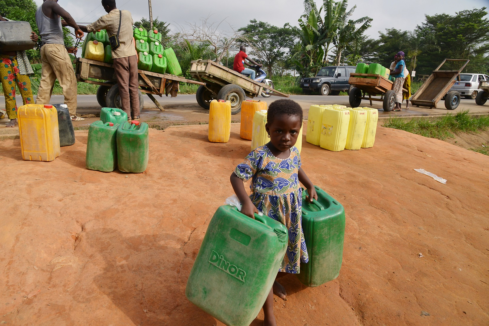 Menina carrega dois galões de água na região de Abobo, em Abidjan, na Costa do Marfim. Os países da África estão entre os que mais sofrem com a escassez de água. Foto Issouf Sanogo/AFP