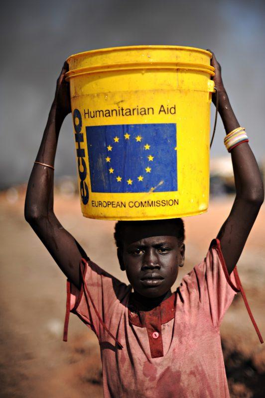 Jovem carrega um balde de água na cabeça, na região central do Sudão. Foto Roberto Schmidt/AFP