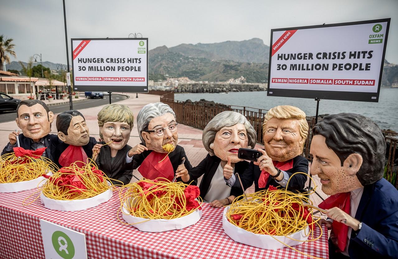 Ativistas da Oxfam usam máscaras com os rostos de lideranças mundiais para protestar contra a fome na África. Foto Michael Kappeler/DPA