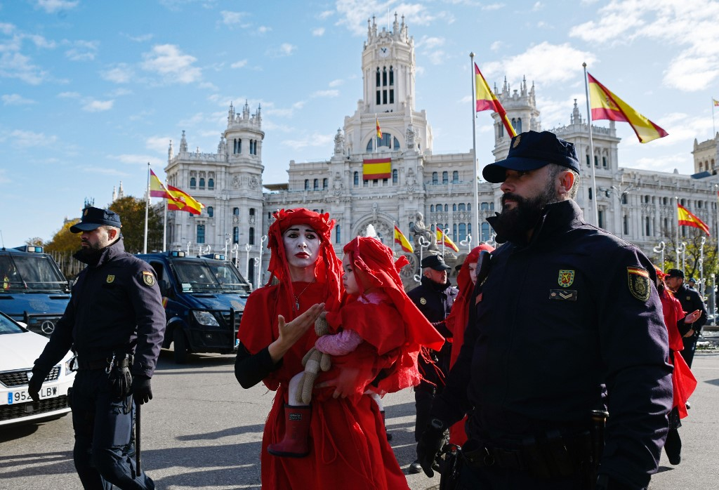 Police officers walk beside global environmental movement Extinction Rebellion activists during a protest at the Cibeles square in Madrid, on December 3, 2019. - Spain's Socialist government offered to host this year's UN climate conference, known as COP25, from December 2 to December 13, 2019, after the event's original host Chile withdrew last month due to deadly riots over economic inequality. (Photo by OSCAR DEL POZO / AFP)