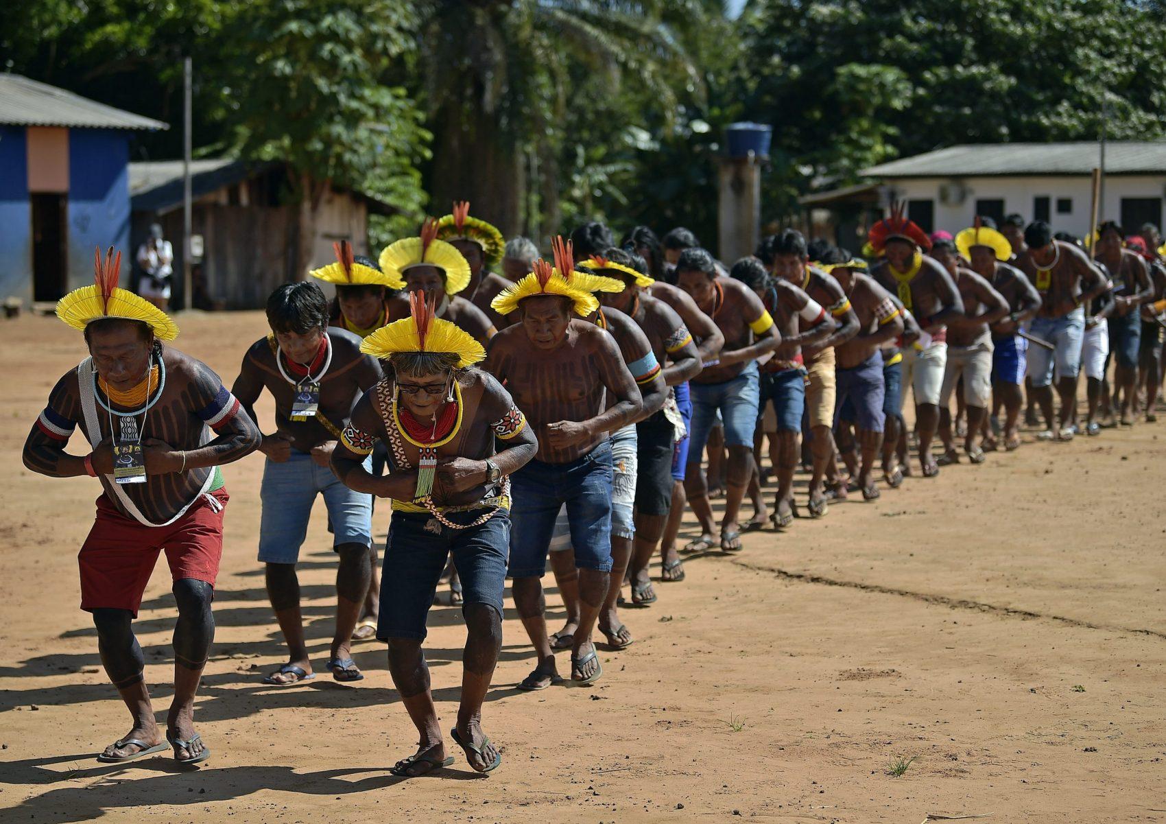 Indígenas dançam em homenagem a Raoni, na Capoto Jarina, terra indígena cortada por uma estrada por onde trafegam carretas de soja e gado: floresta afetada pelo desmatamento dos dois lados da via (Foto: Carl de Souza/AFP)