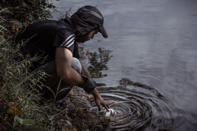 Professor Miguel Felippe coleta água do rio Paraopeba, em Felixlândia durante a expedição: contaminação com impactos ainda incalculáveis (Foto: Maria Otávia Rezende/UFJF)