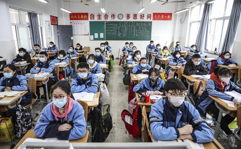 Alunos do ensino médio da cidade de Huaian, na província de Jiangsu, leste da China, começam a retomar às aulas após o fim da quarentena. Foto STR / AFP