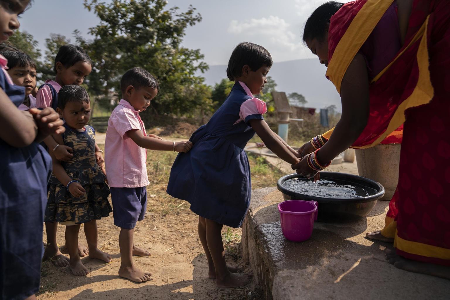 Crianças fazem fila para lavar as mãos do lado de fora de uma escola na Índia. Foto Unicef
