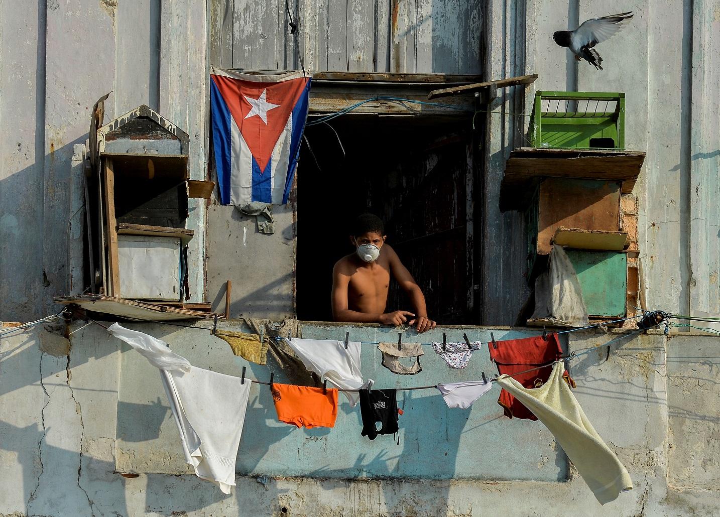 Homem usa máscara facial na varanda em Havana. As autoridades cubanas dizem que o embargo econômico dos EUA vem dificultando o combate à covid-19. Foto Yamil Lage/AFP