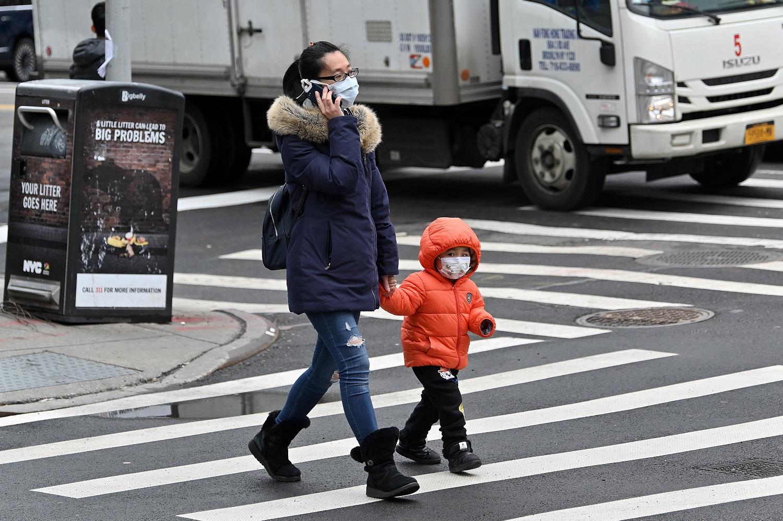 Ódio e preconceito contra asiáticos: Mulher e criança usando máscaras protetoras são vistas atravessando a rua em Chinatown, Nova York. As mulheres são as mais afetadas pelo preconceito. Foto Dia Dipasupil/Getty Images/AFP