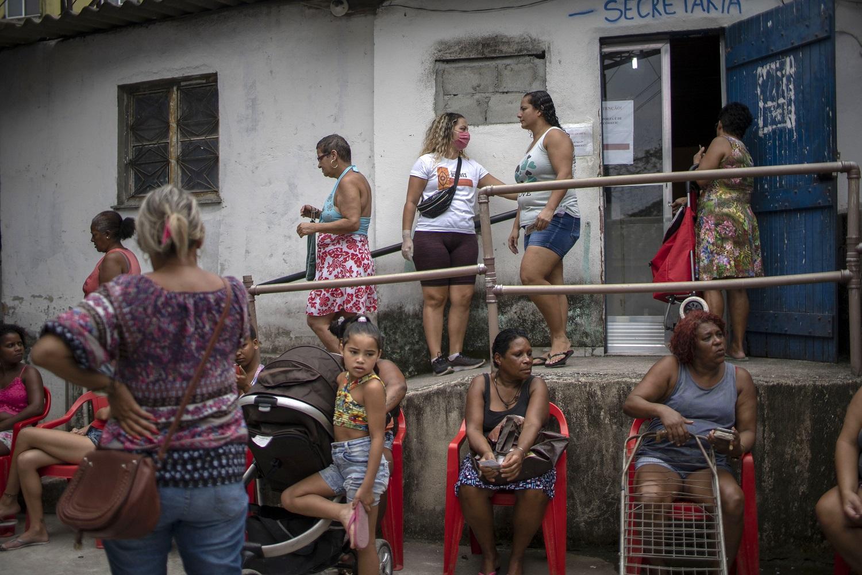 Moradores da Cidade de Deus aguardam a doação de alimentos feita por uma ONG na comunidade durante a pandemia. Foto Mauro Pimental/AFP