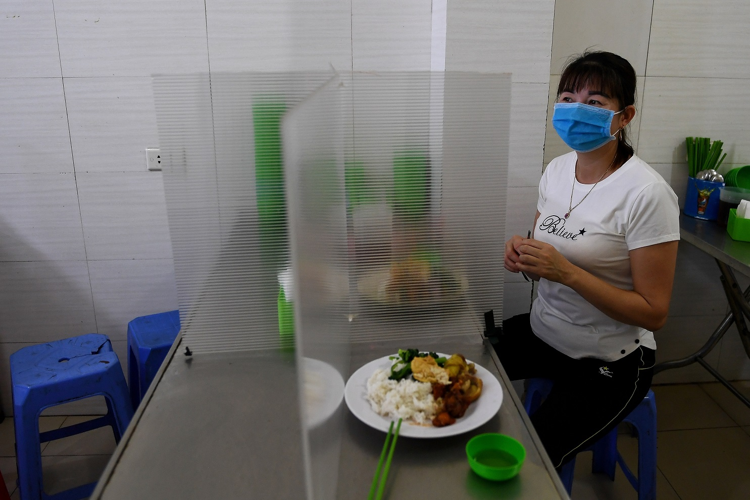 Em Hanoi, no Vietnã, uma divisória de plástico no restaurante serve como mais uma medida de prevenção contra o coronavírus. Foto Nhac Nguyen/AFP