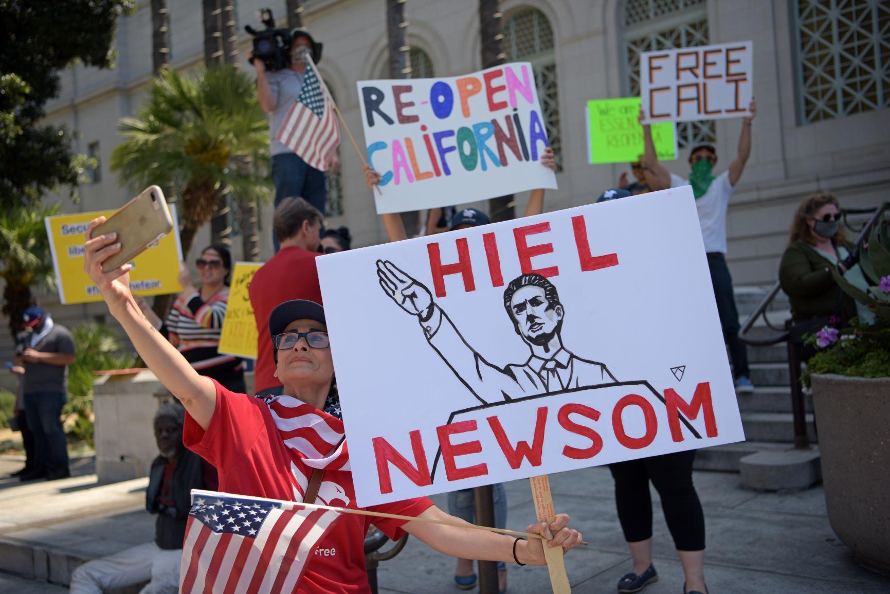 """Cartaz compara o governador da Califórnia, Gavin Newsome, a nazista em protesto contra lockdown em Los Angeles: governadores democratas são acusados de """"tirania"""" (Foto: Agustin Paullier/AFP)"""
