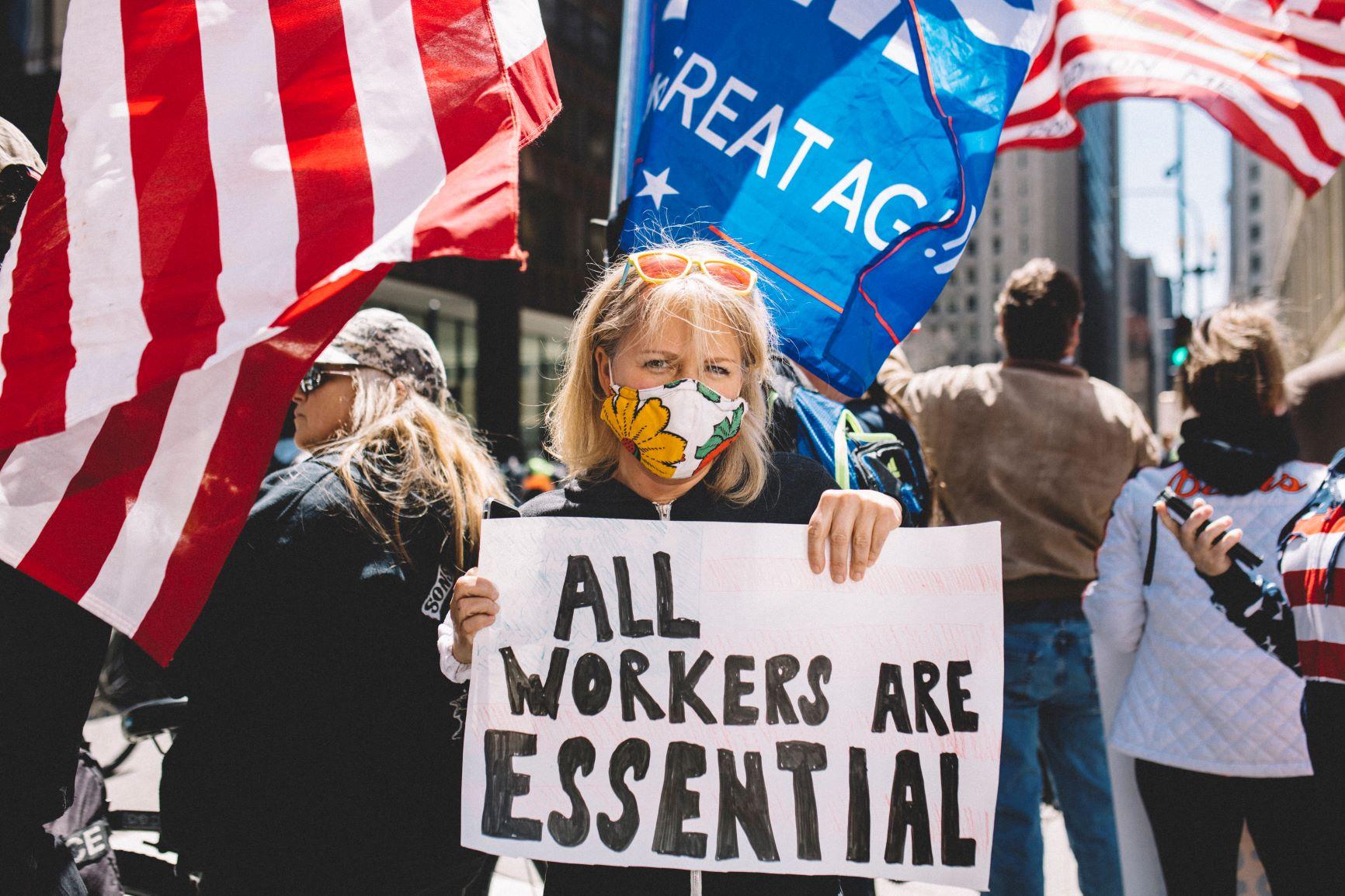 """Mulher protesta em Chicago com cartaz """"Todos os trabalhadores são essenciais"""": manifestantes não falam de pobreza (Jim Vondruska/NurPhoto/AFP)"""