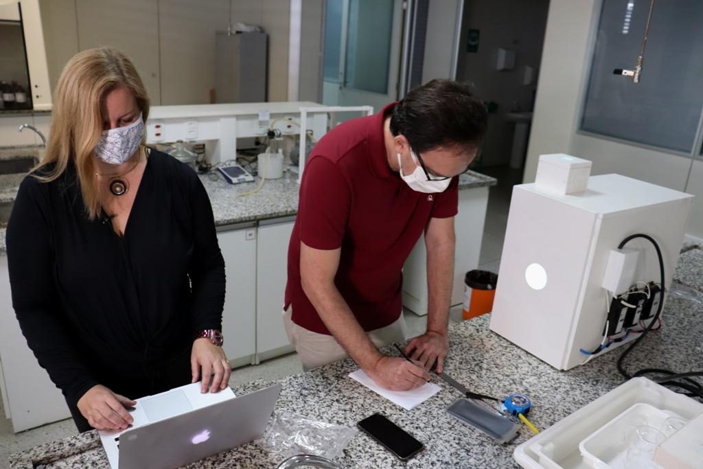 Os professores Suellen Lattes e Joatan Rodrigues no laboratório da UFS: tecnologia, com uso de radiação, permite a reutilização do equipamento de proteção individual no enfrentamento à covid-19 (Foto: Josafá Neto)