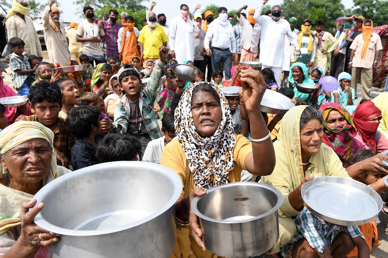 Nos arredores de Amritsar, na Índia, migrantes de Maharastra seguram utensílios de cozinha enquanto protestam contra o governo pela falta de comida durante a pandemia. Foto Narinder Nanu/AFP