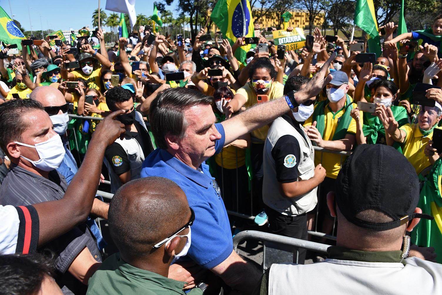 Enquanto o Brasil chora os seus mortos, o presidente Jair Bolsonaro segue celebrando com seus seguidores em manifestações cotidianas em Brasília. Foto Evaristo Sá/AFP