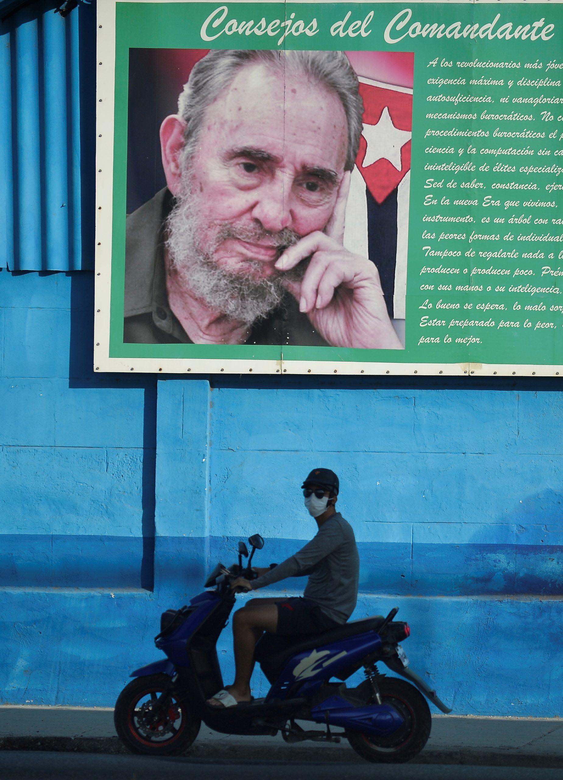Homem de máscara passa de lambreta, em frente à imagem de Fidel Castro: Havana começa a flexibilizar isolamento. Foto de Yamil Lage (AFP)