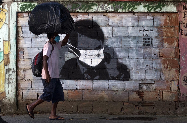 Grafite no Rio de Janeiro mostra o presidente Bolsonaro usando máscara contra a covid-19 sobre o olhos. Foto Bárbara Dias/AGIF