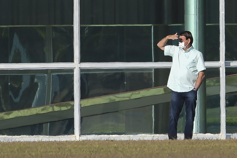 Jair Bolsonaro gesticula do lado de fora do Palácio da Alvorada, em Brasília. O presidente testou positivo para o coronavírus em 7 de julho, depois de meses minimizando os perigos da doença. Foto Sergio Lima/AFP