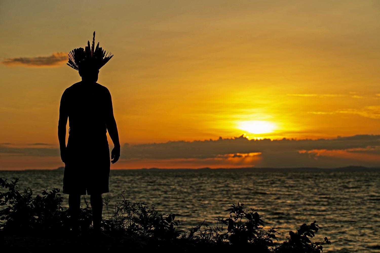 O chefe Leno da tribo Kunaruara assiste o nascer do sol ao lado do rio Tapajós, no município de Santarém, no oeste do Pará. Sua tribo vive em uma área remota e ainda não foi atingida pelo coronavírus. Foto Tarso Sarraf/AFP