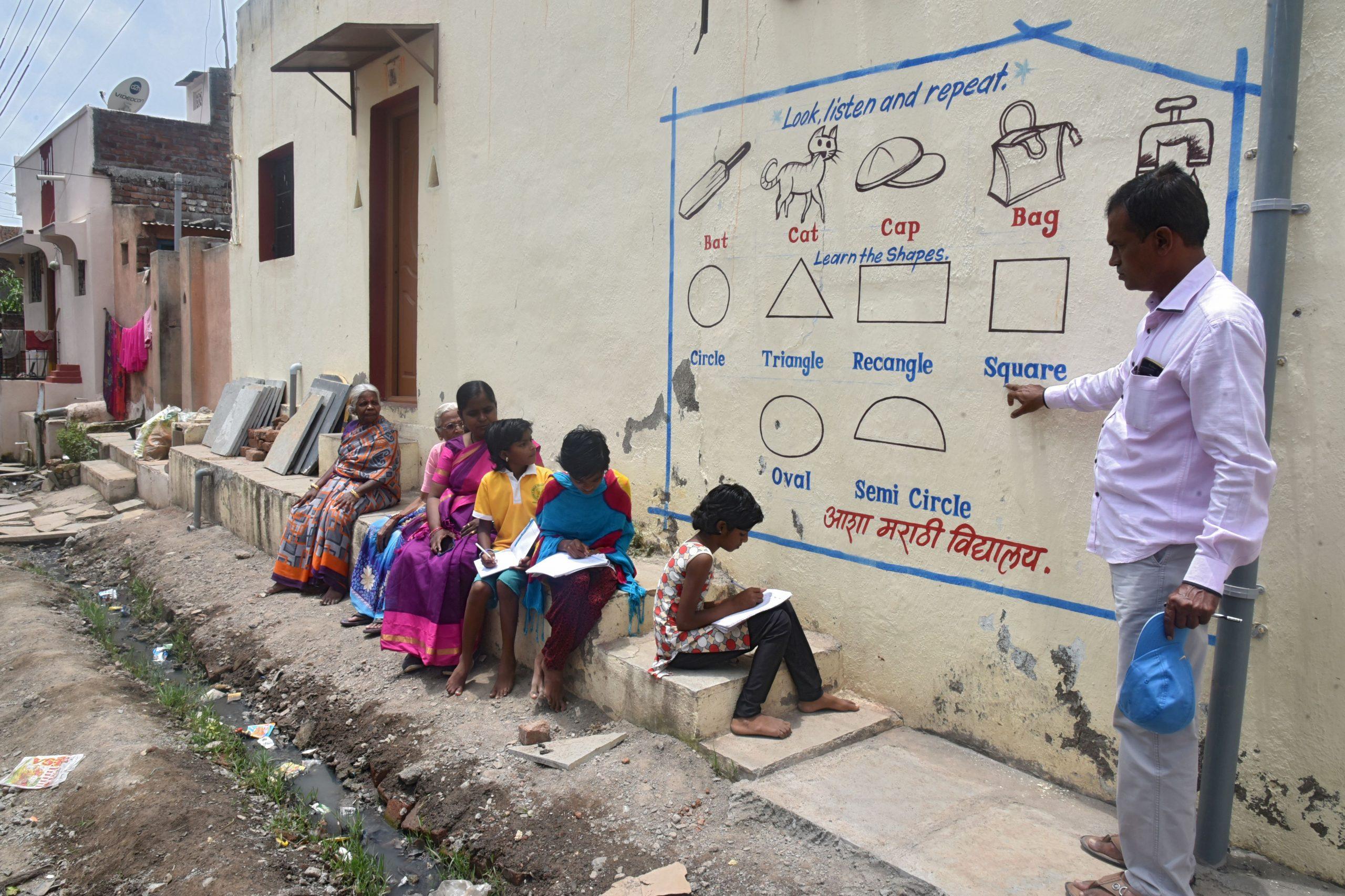Professor usa parede de casa para dar aula a crianças sem acesso à internet em Solapur, na Índia: 1,5 bilhão de crianças fora da escola no pico da pandemia em todo o mundo (Foto: AFP)