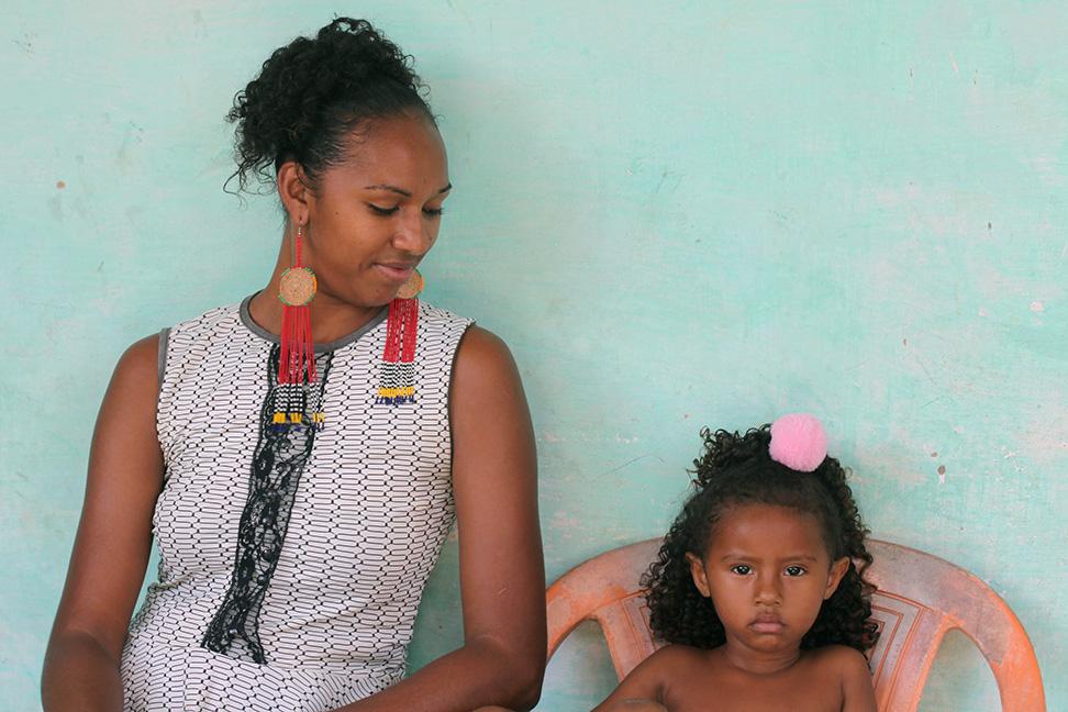 Ana Tássia com a pequena Allana: quando sai para trabalhar, mãe deixa menina com a avó, que planta hortaliças na roça da comunidade (Foto: Djuena Tikuna)