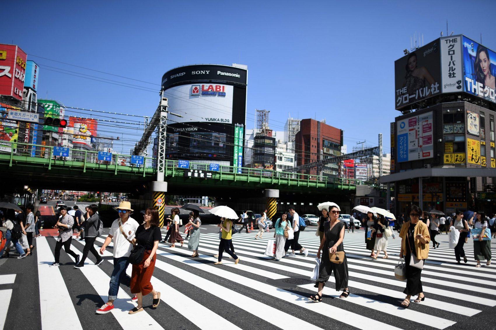 Moradores de Tóquio usam sombrinhas para se proteger de sol no último verão: diferença das ilhas de calor para pontos mais frescos da capital japonesa chega a cinco graus centígrados (Foto: Charly Triballeau/AFP)