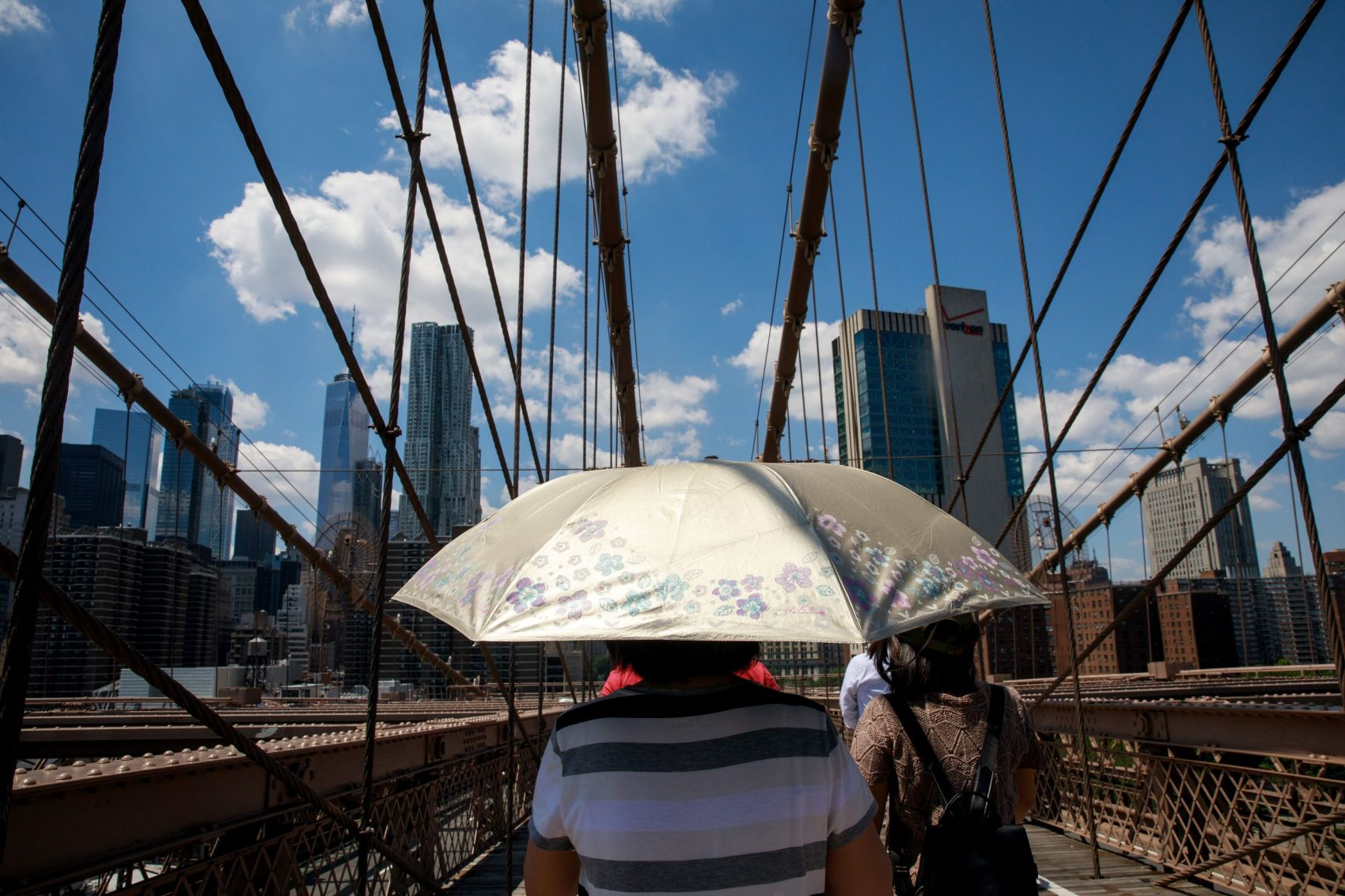 Moradora se protege do sol na ponte do Brooklyn, em Nova YorK: cidade tem abrigos para proteger os mais vulneráveis do calor intenso (Foto: Drew Angerer/AFP)