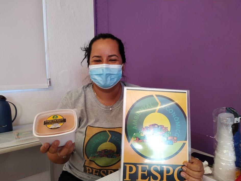 Joana Almeida e o sabão produzido pelos voluntários do Pespc - Projeto de Educação Social e Pensamento Consciente: distribuição na comunidade para divulgar produto (Foto: Arquivo Pessoal)
