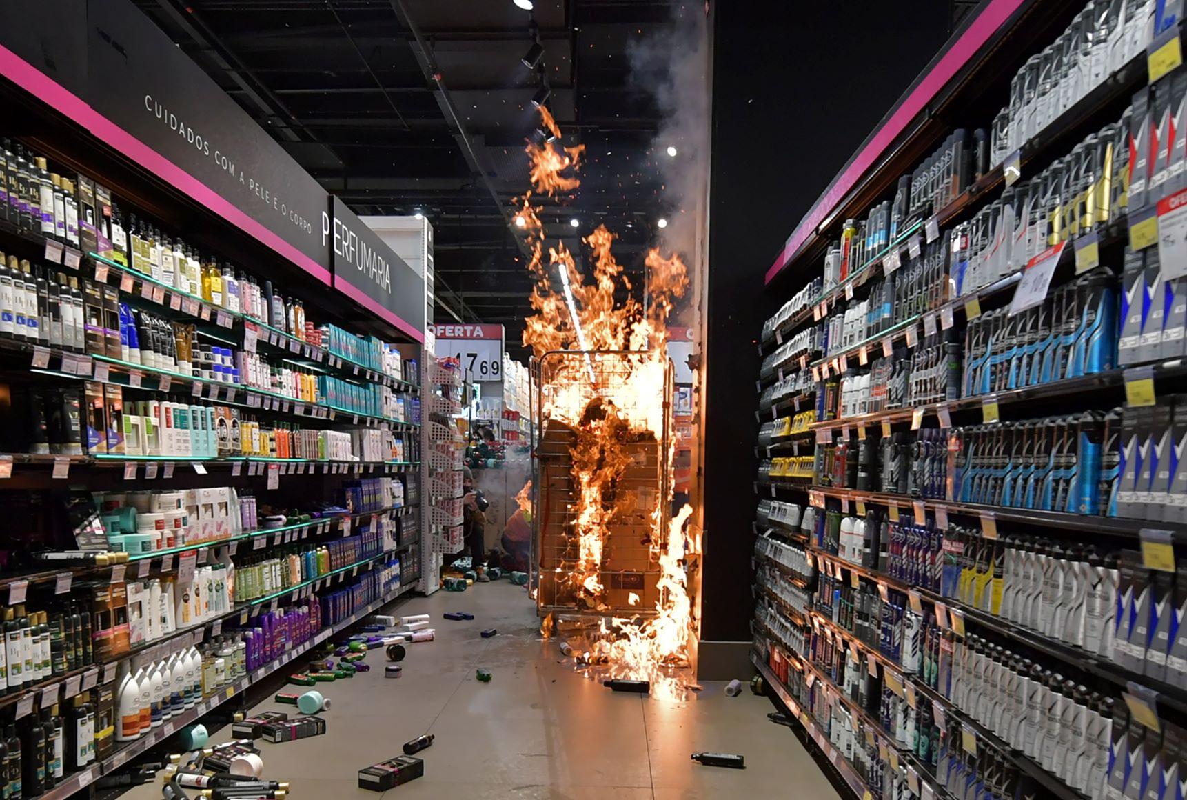 Produtos incendiados em loja do Carrefour em São Paulo: manifestantes também quebraram vidros e depredaram carros em protesto contra assassinato de soldador por seguranças no Sul (Nelson Almeida/AFP)