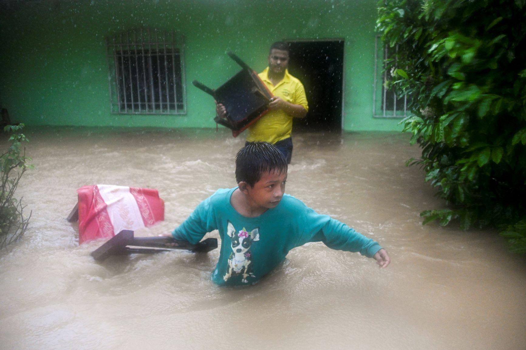 Pai e filho resgatam móveis de casa no norte da Guatemala na passagem do Eta: furacões mais frequentes e mais destrutivos com aquecimento global (Foto: Johann Ordoñez/AFP)