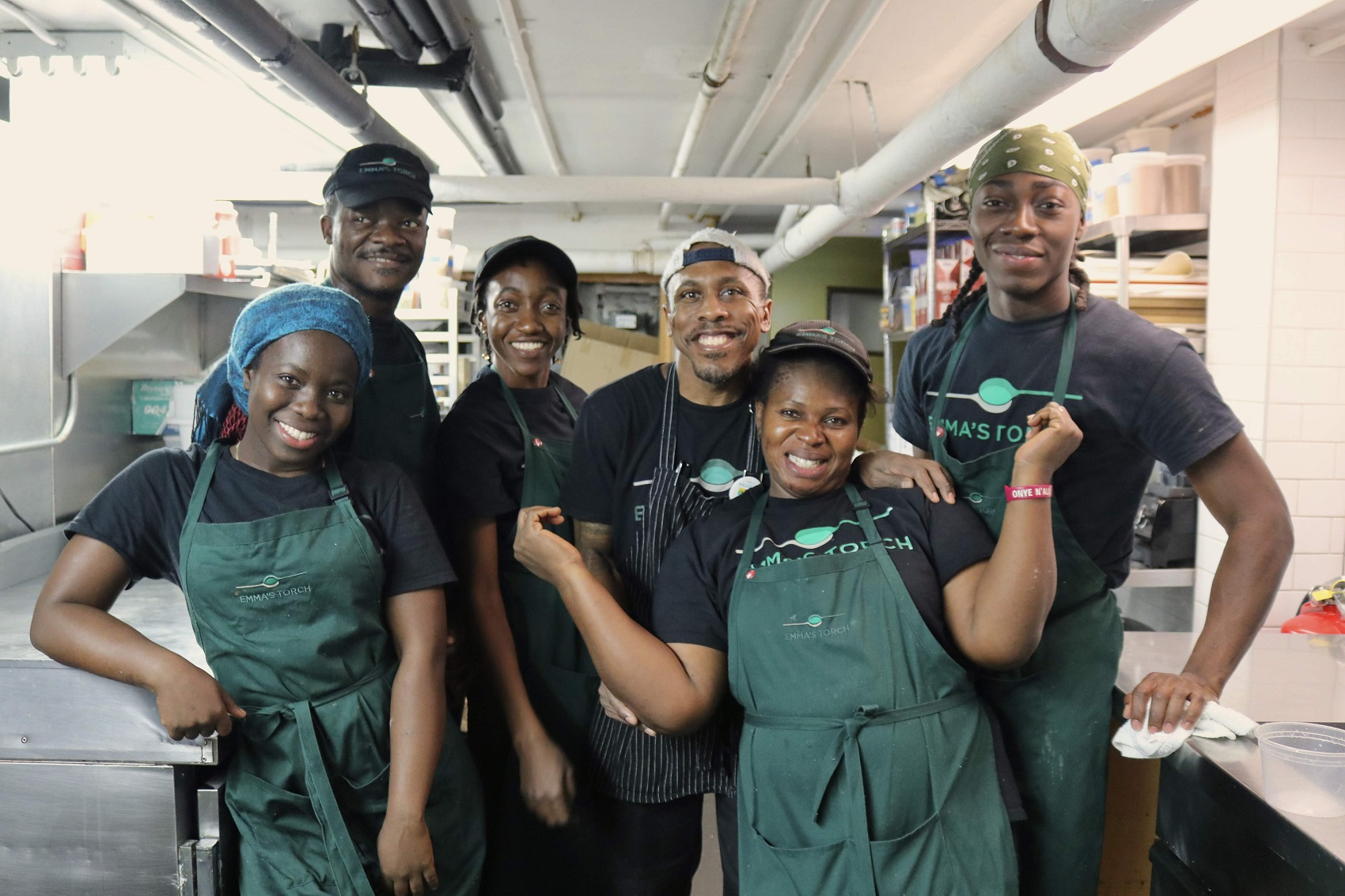 O chef Alex Harris (centro), diretor culinário da Emma's Torch e seus pupilos: escola de culinária que virou também restaurante de sucesso (Foto: Divulgação)