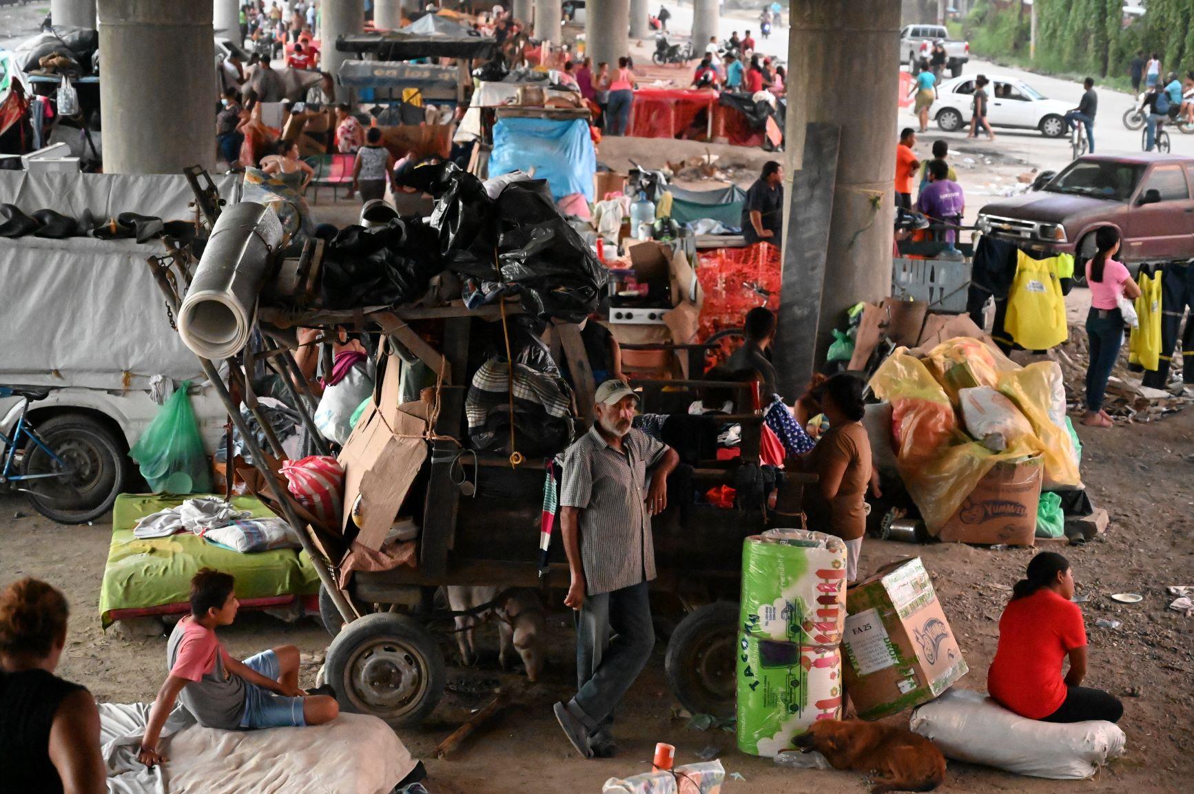 Pessoas que perderam suas casas abrigadas sob uma ponte dias após a passagem do furacão Iota em San Pedro Sula: tempestades afetaram mais de 7 milhões na América Central (Foto: Orlando Sierra/AFP)