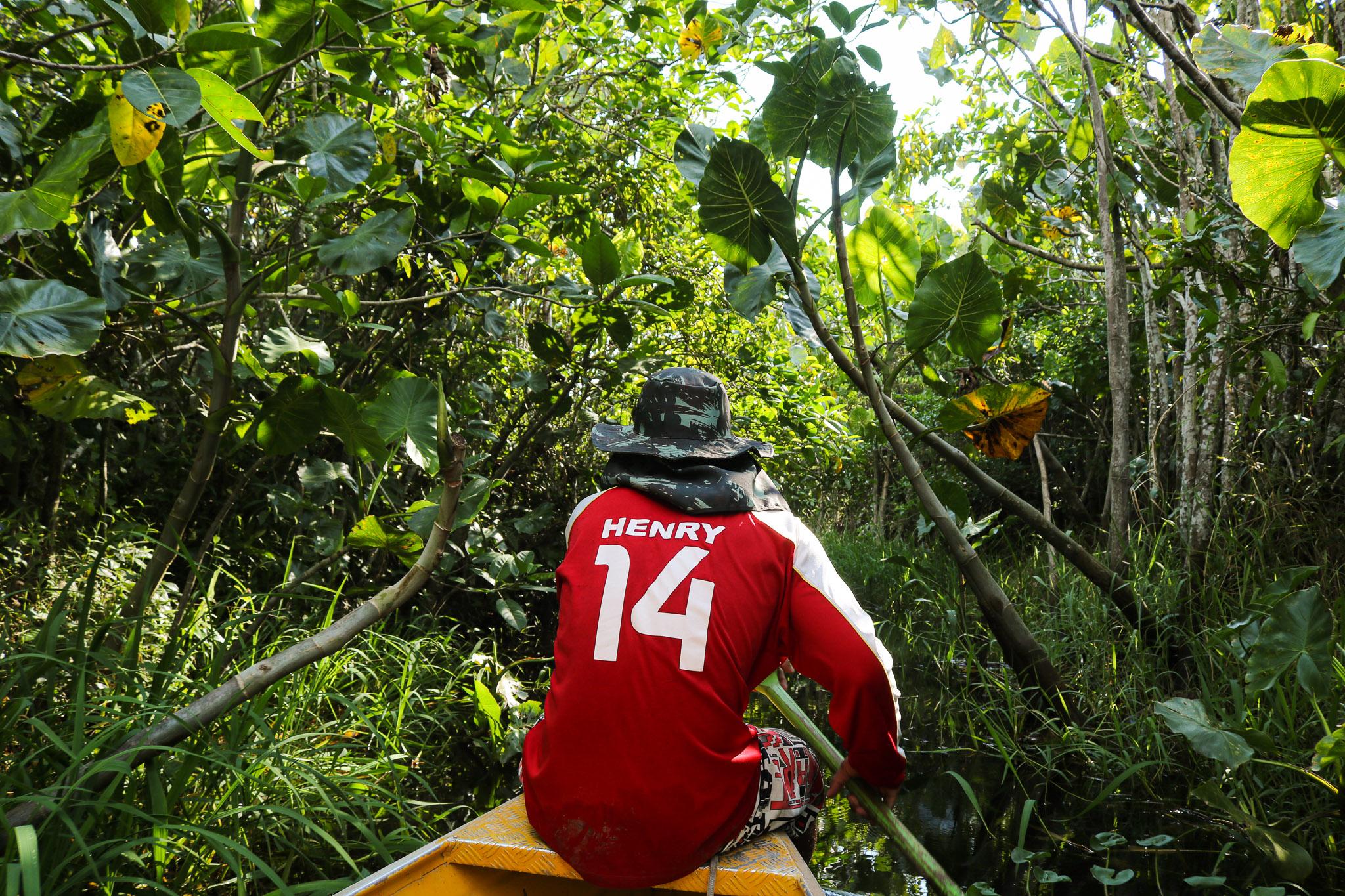 Ruan leva apostilas no acesso à casa de Geiliane em tempos de seca: na cheia, rio esconde quase toda a vegetação e facilita o transporte (Foto: Bruno Tadeu)