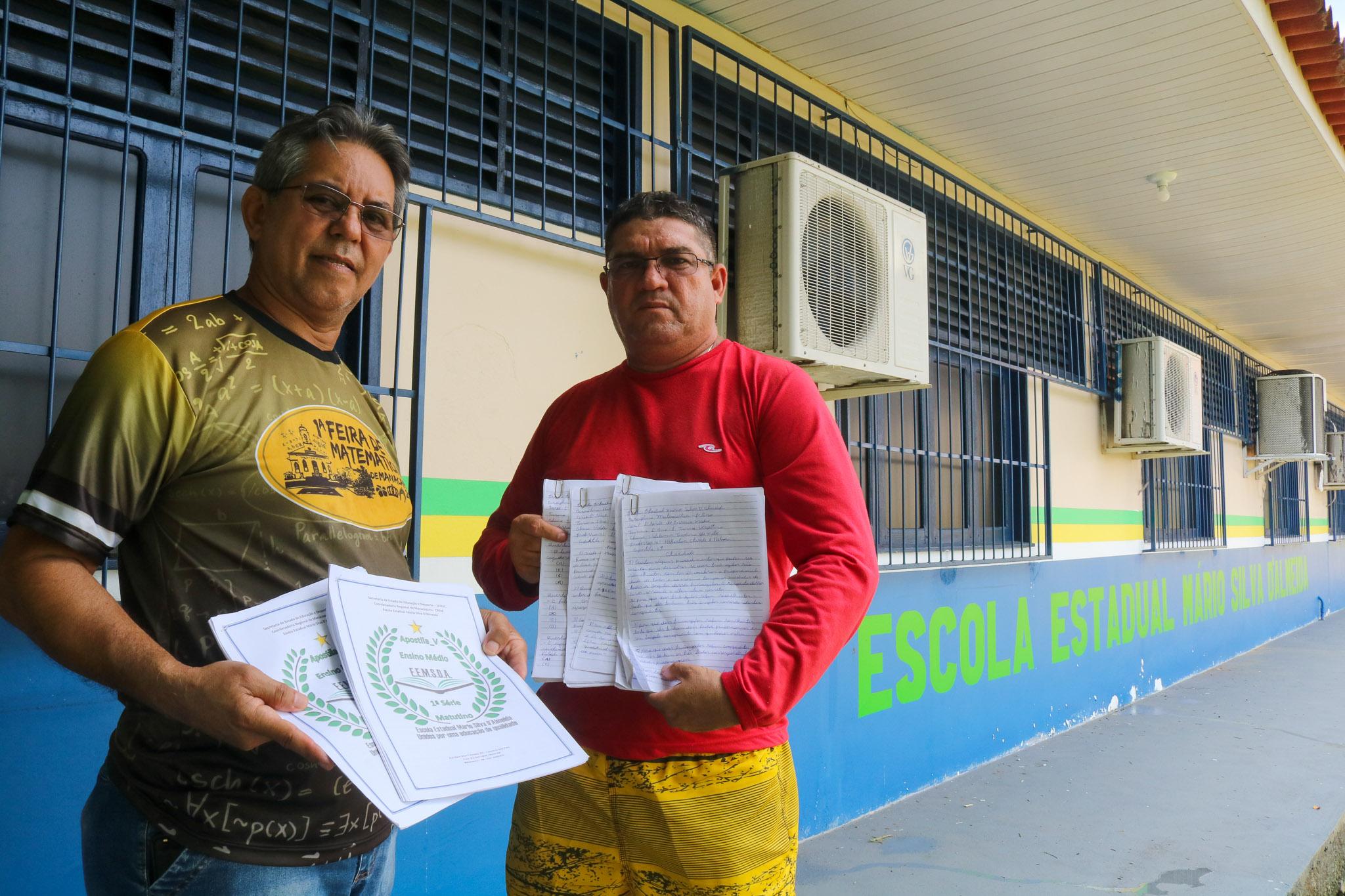 O professor Hayrson (à direita) com o gestor Mackson e as apostilas: entregador de apostilas com aulas improvisadas nas comunidades isoladas (Foto: Bruno Tadeu)