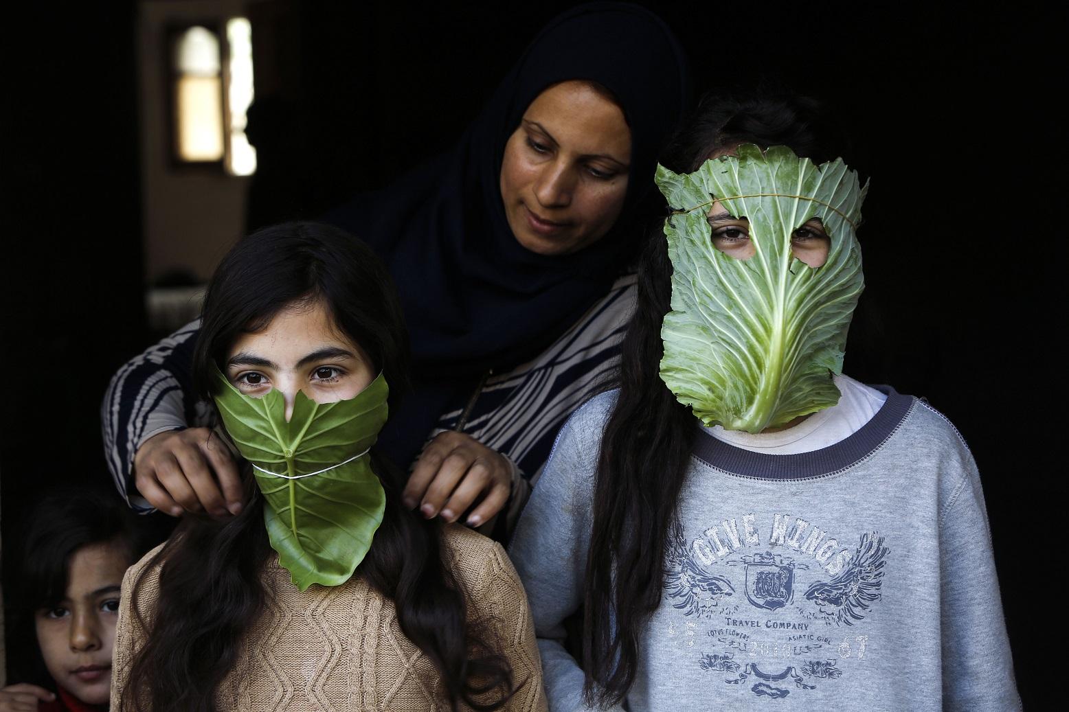 Uma mãe palestina entretém seus filhos com máscaras improvisadas feitas de repolho enquanto cozinha em Beit Lahia, no norte da Faixa de Gaza. Foto Mohammed Abed/AFP. Abril de 2020